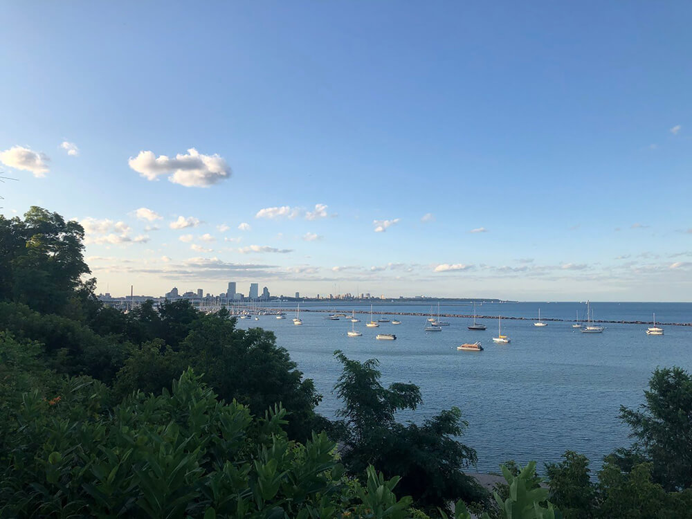 Early-evening blue skies and boats anchored on Lake Michigan, with the Milwaukee city skyline in the background.
