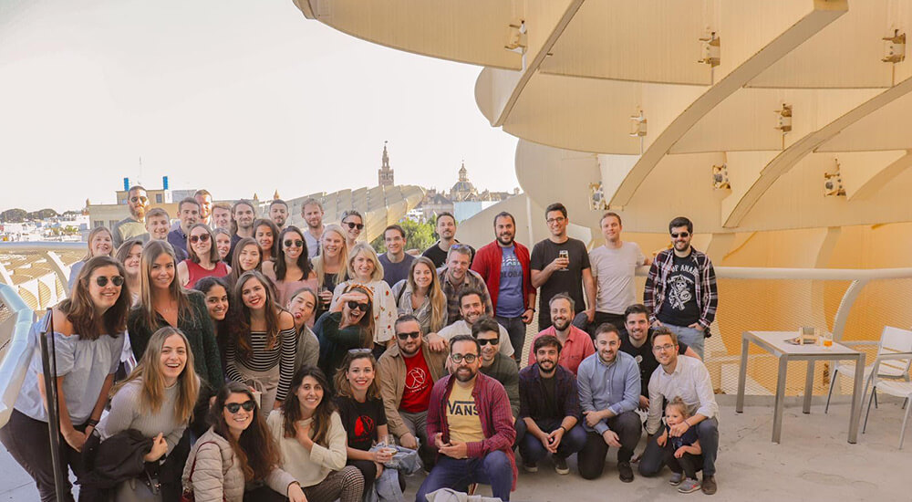 A group photo of the Glamping Hub team celebrating on the Metropol Parasol terrace in Seville, Spain.