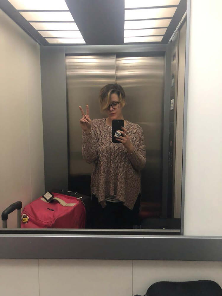 The writer giving a peace sign in an elevator mirror, surrounded by three big suitcases.